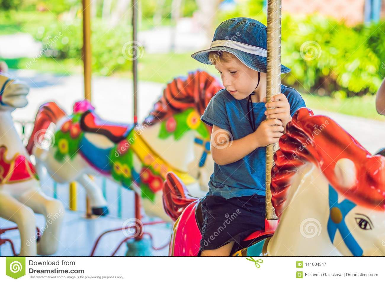 Cute little boy enjoying in funfair and riding on colorful carousel house