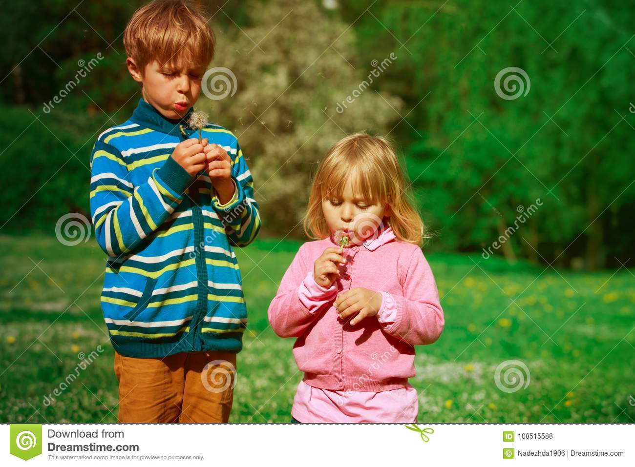Little boy and girl blow dandelions, play in spring nature