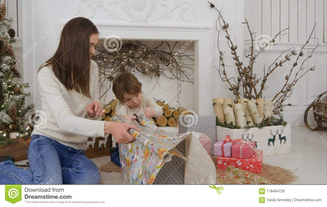 cute little boy helping his mother to cut paper for wrapping up