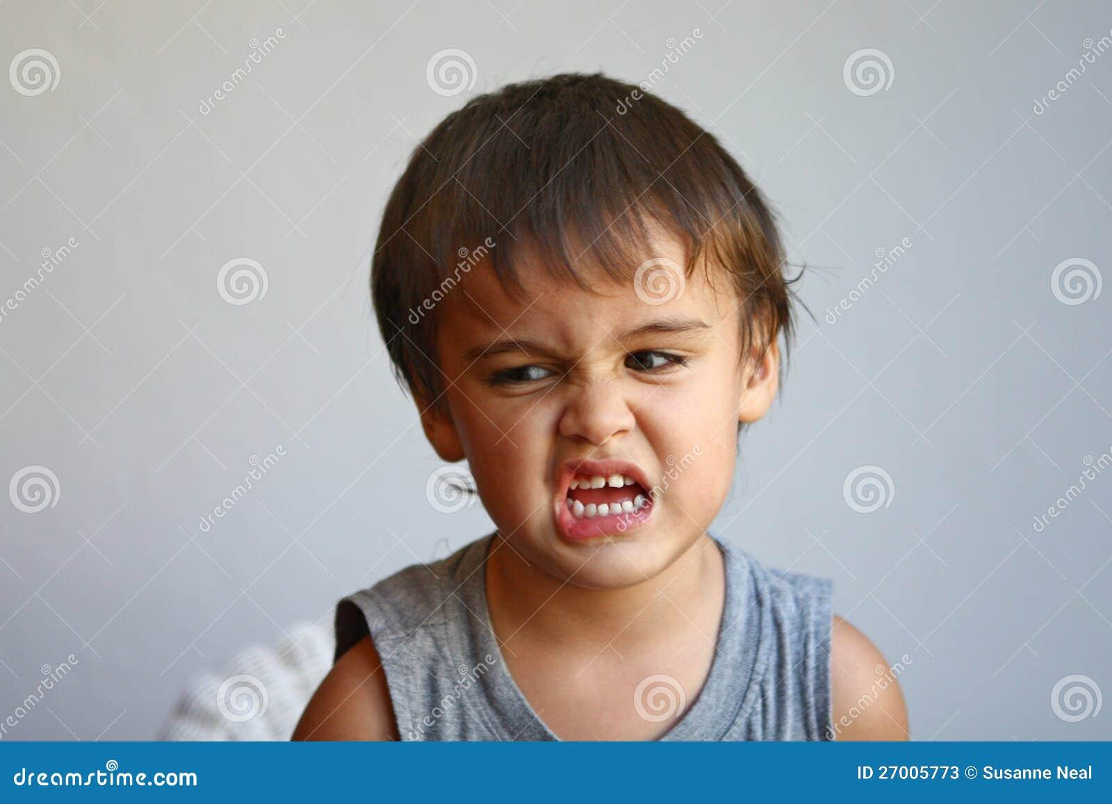 cute little boy makes face showing eww stock photos