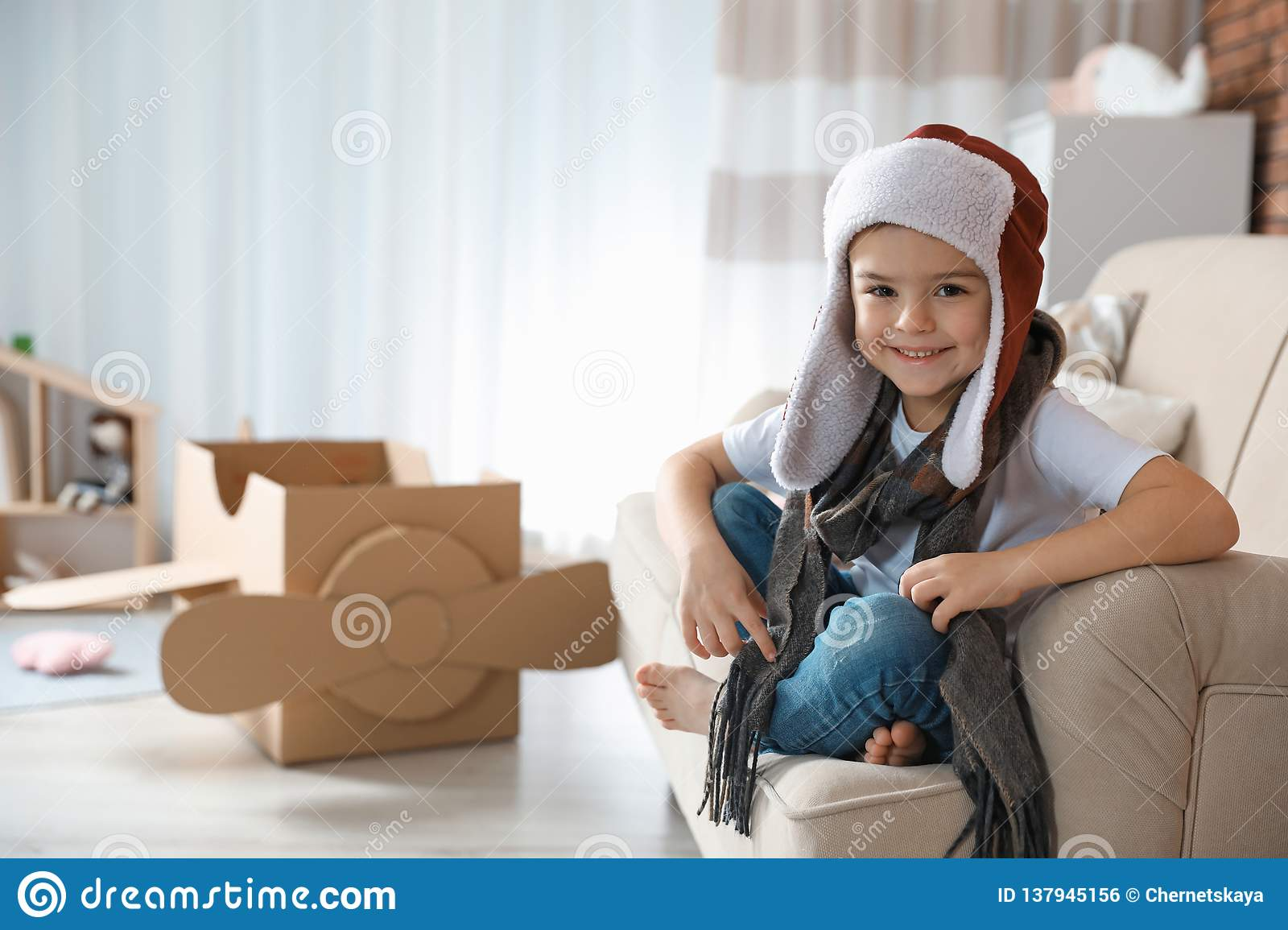 Cute little boy in pilot hat and blurred cardboard airplane on background.