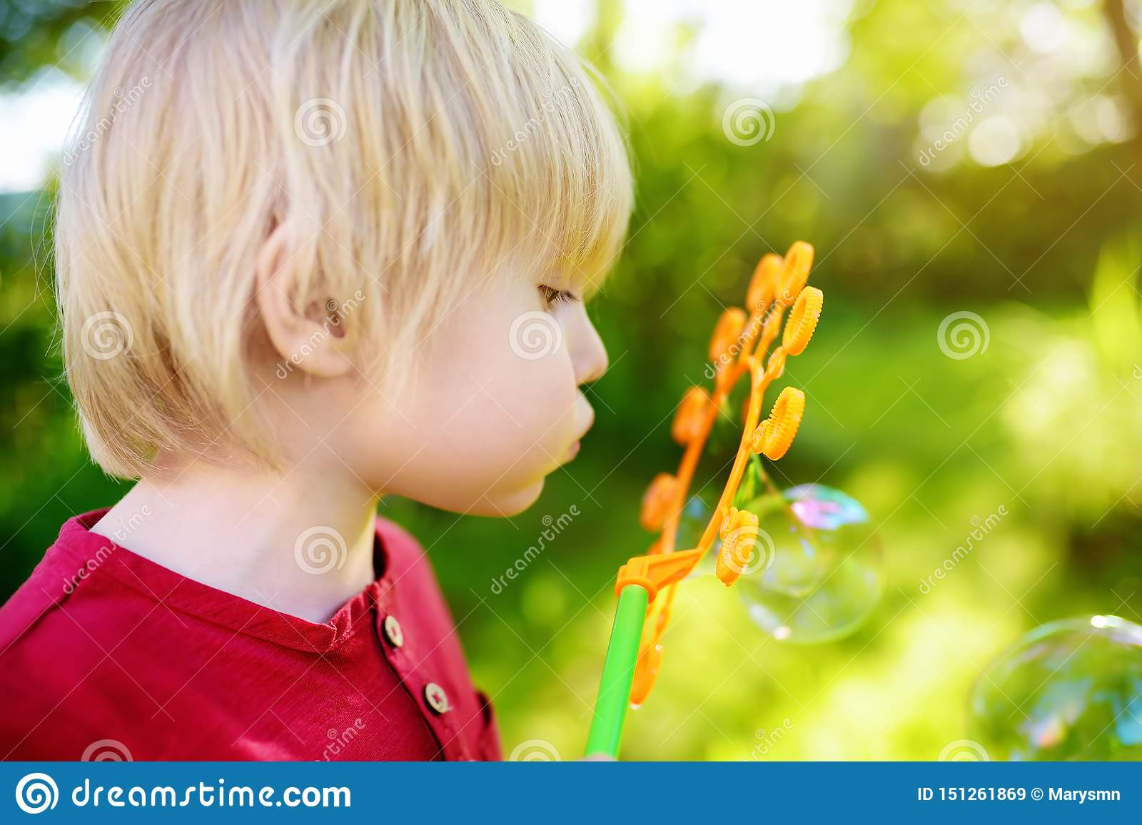 Cute little boy is playing with big bubbles outdoor. Child is blowing big and small bubbles simultaneously