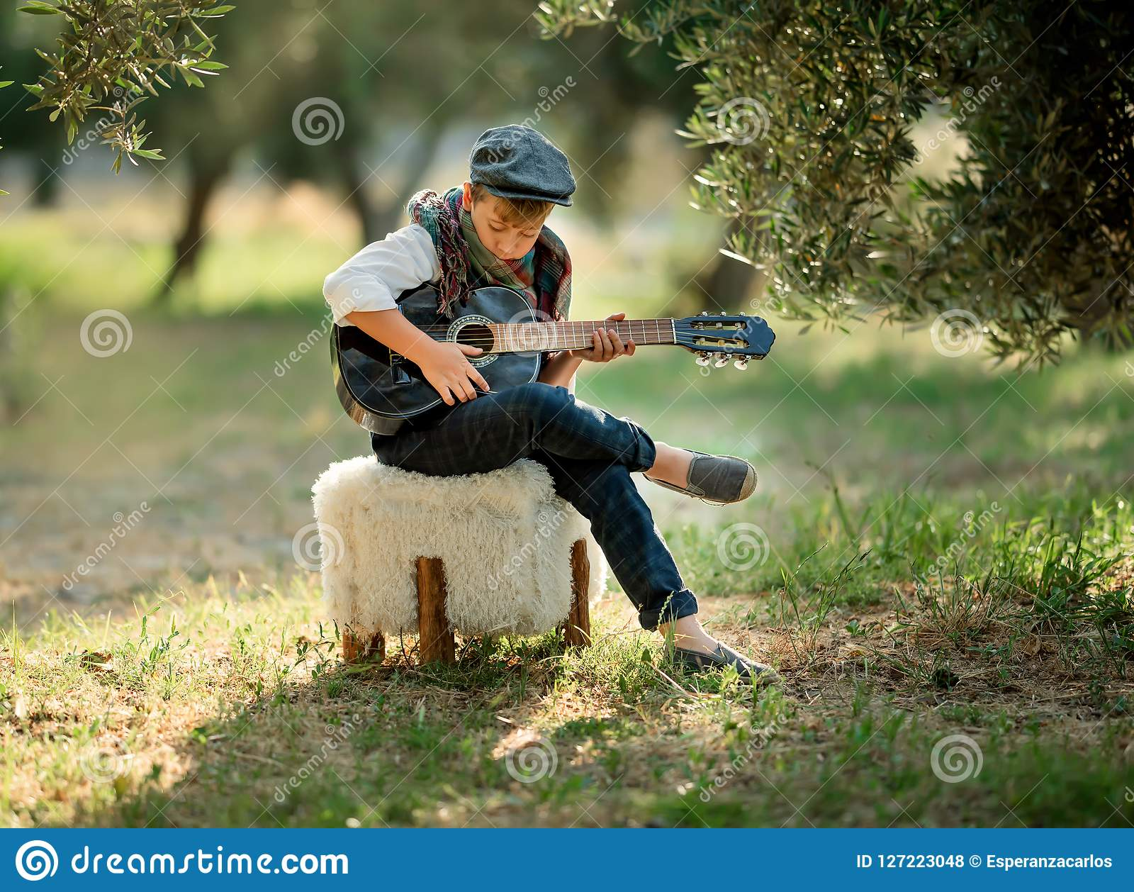 Cute little boy is playing guitar in the park