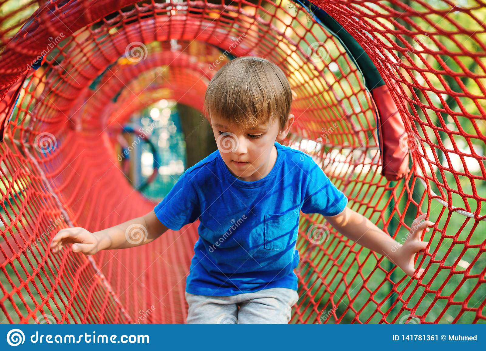 Cute little boy playing outdoors. Child having fun in tunnel at the modern playground. Happy childhood. Summer holidays