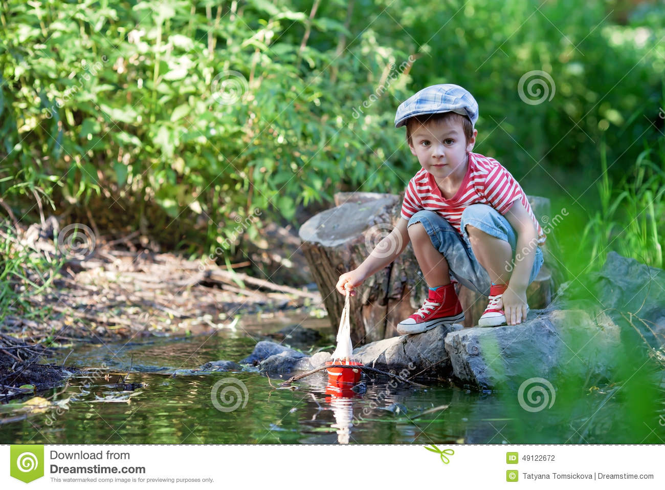 Lillle Boy Toys Boats : Cute little boy playing on a pond with toy boat in hands