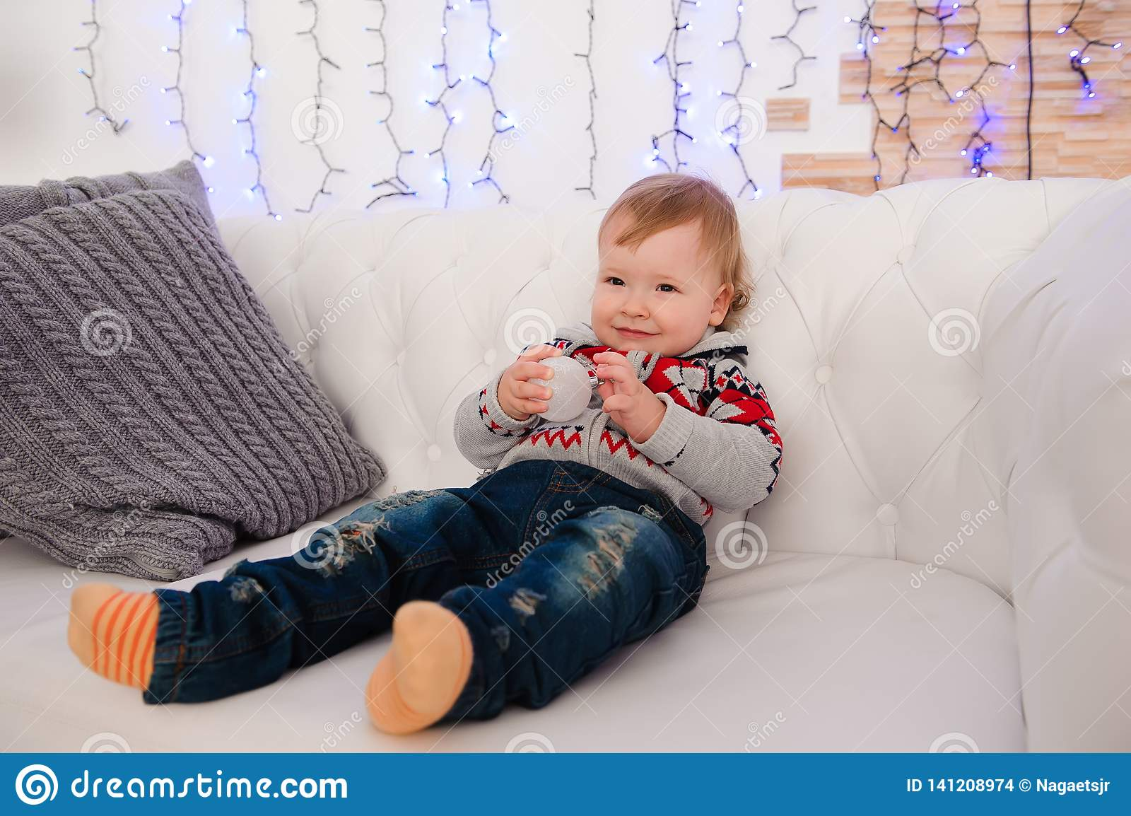 Cute little boy is sitting on the couch at home.