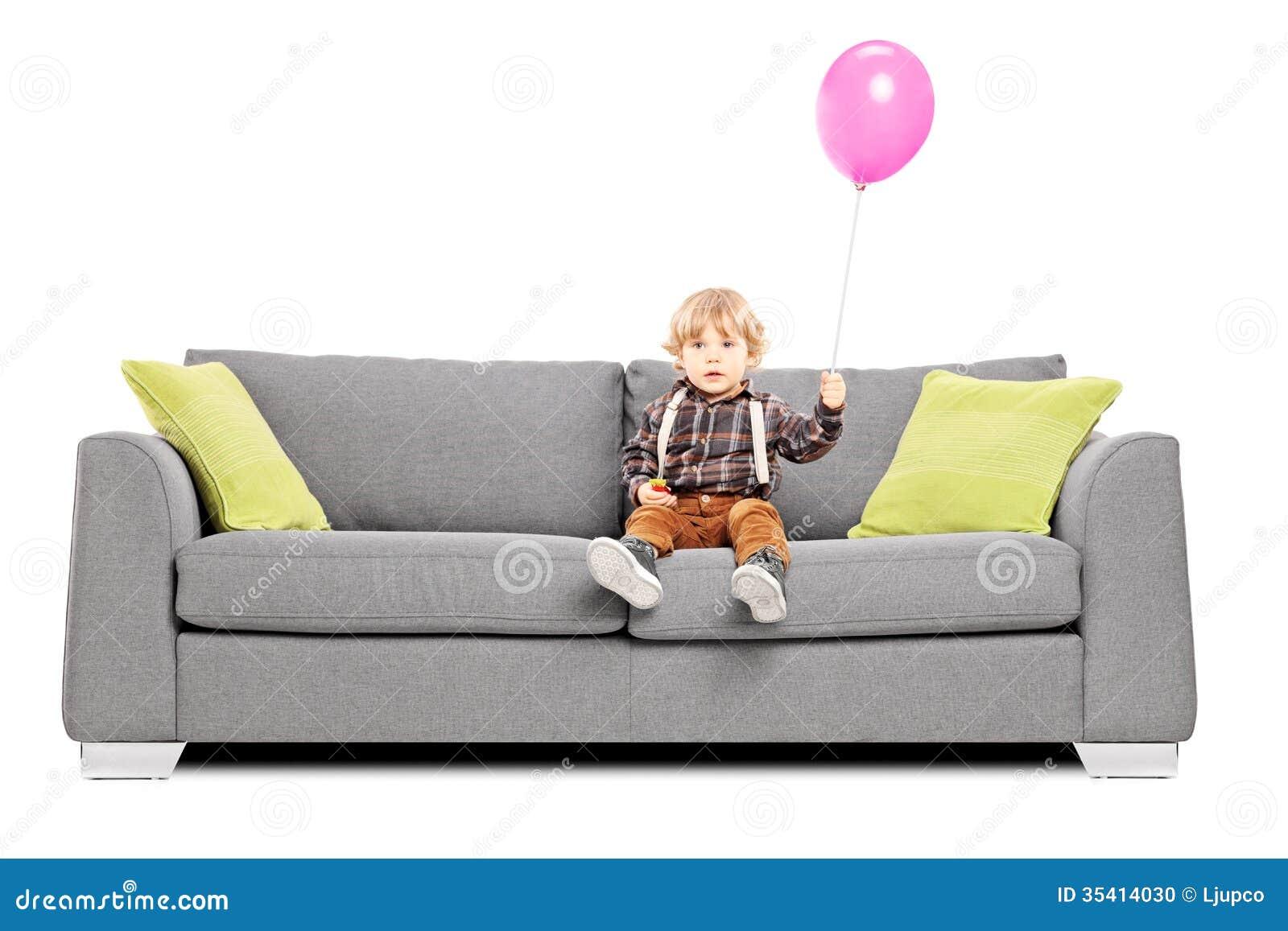 Cute Little Boy Sitting On Sofa With A Hot Air Balloon