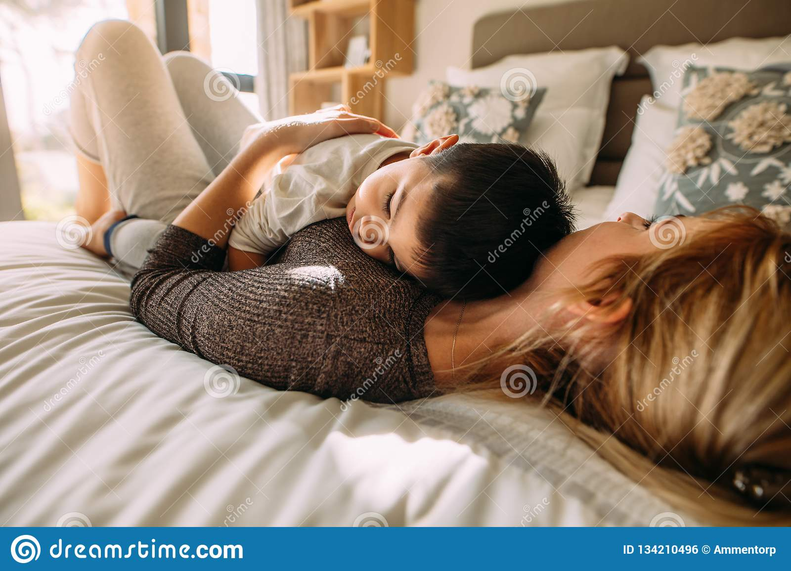 Mother And Son Sleeping Together In Bed Stock Photo