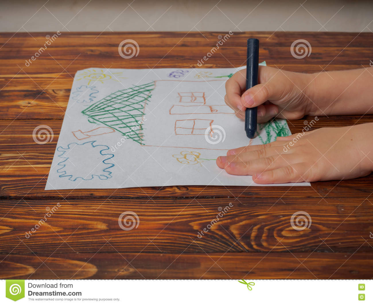 Download cute little boy at the table with his drawing and pencil stock photo image