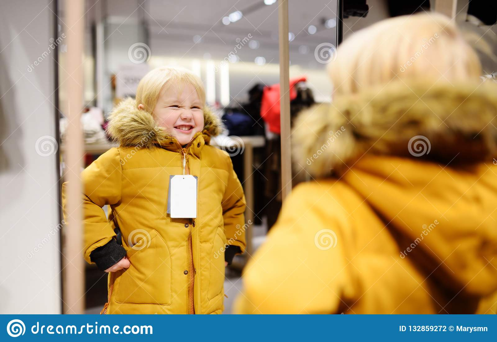 0513c6e43 Cute little boy trying new coat during shopping. Fashion warm clothes for  fall or winter. Kid/child in fitting room or in shopping center/mall