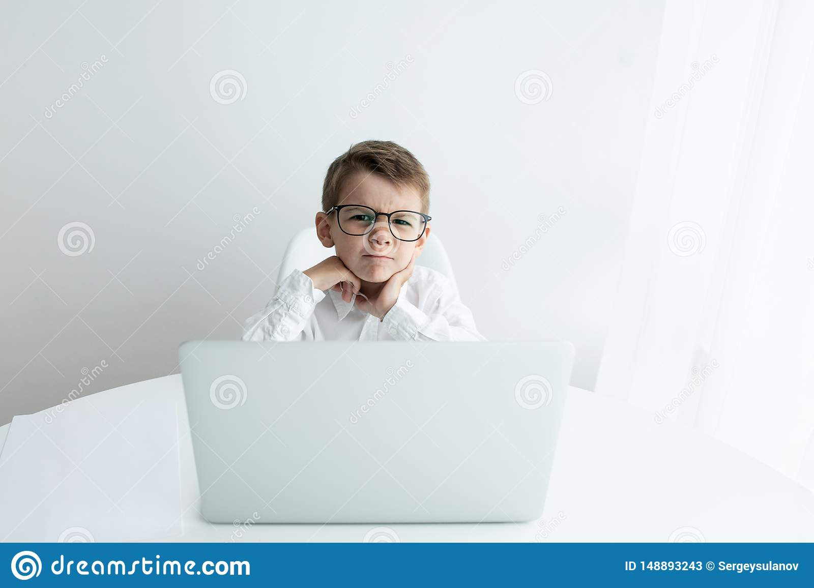 Cute little boy using laptop while doing homework against white background