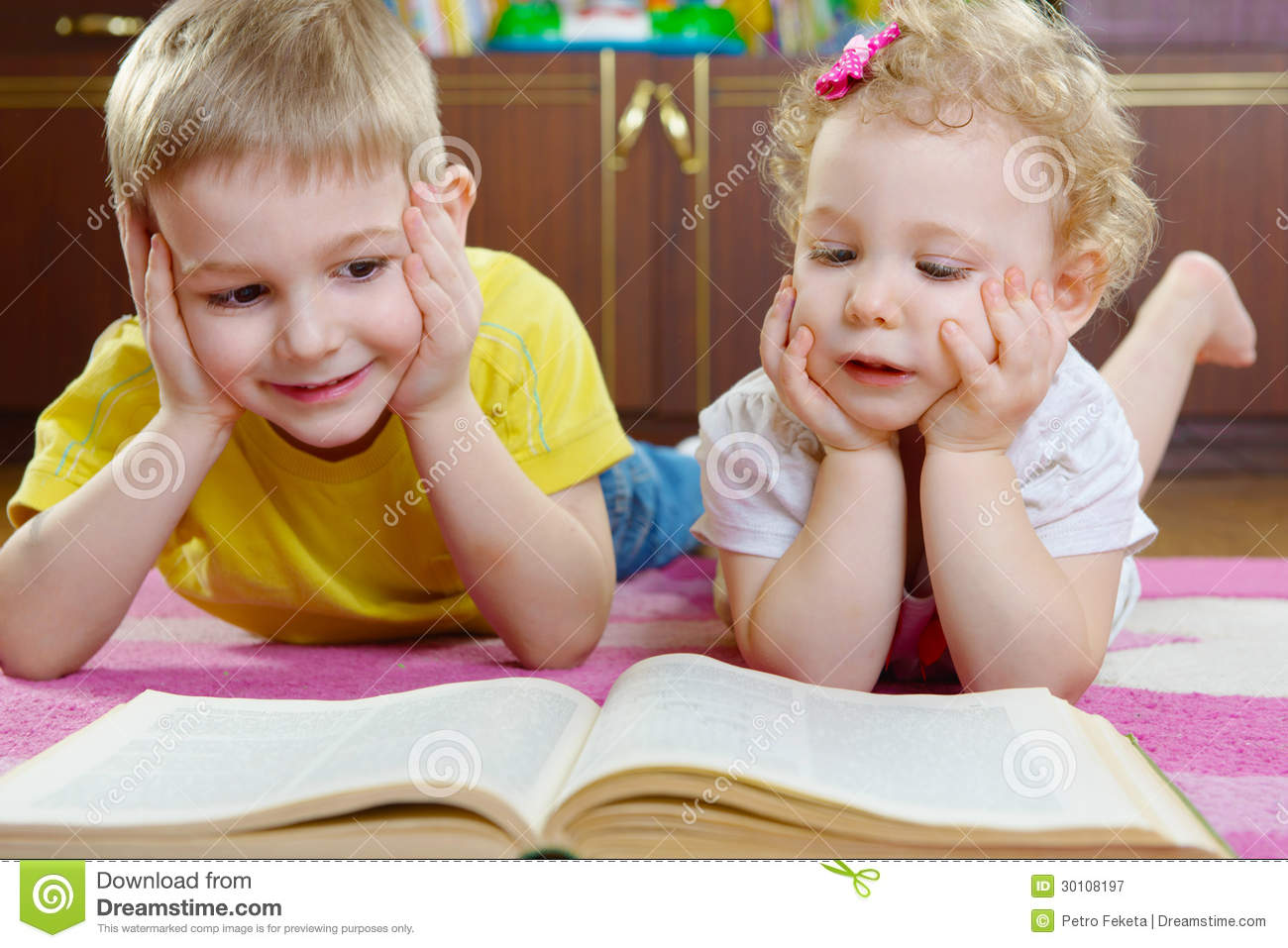 Cute Little Brother And Sister Reading Book On Floor Stock Image