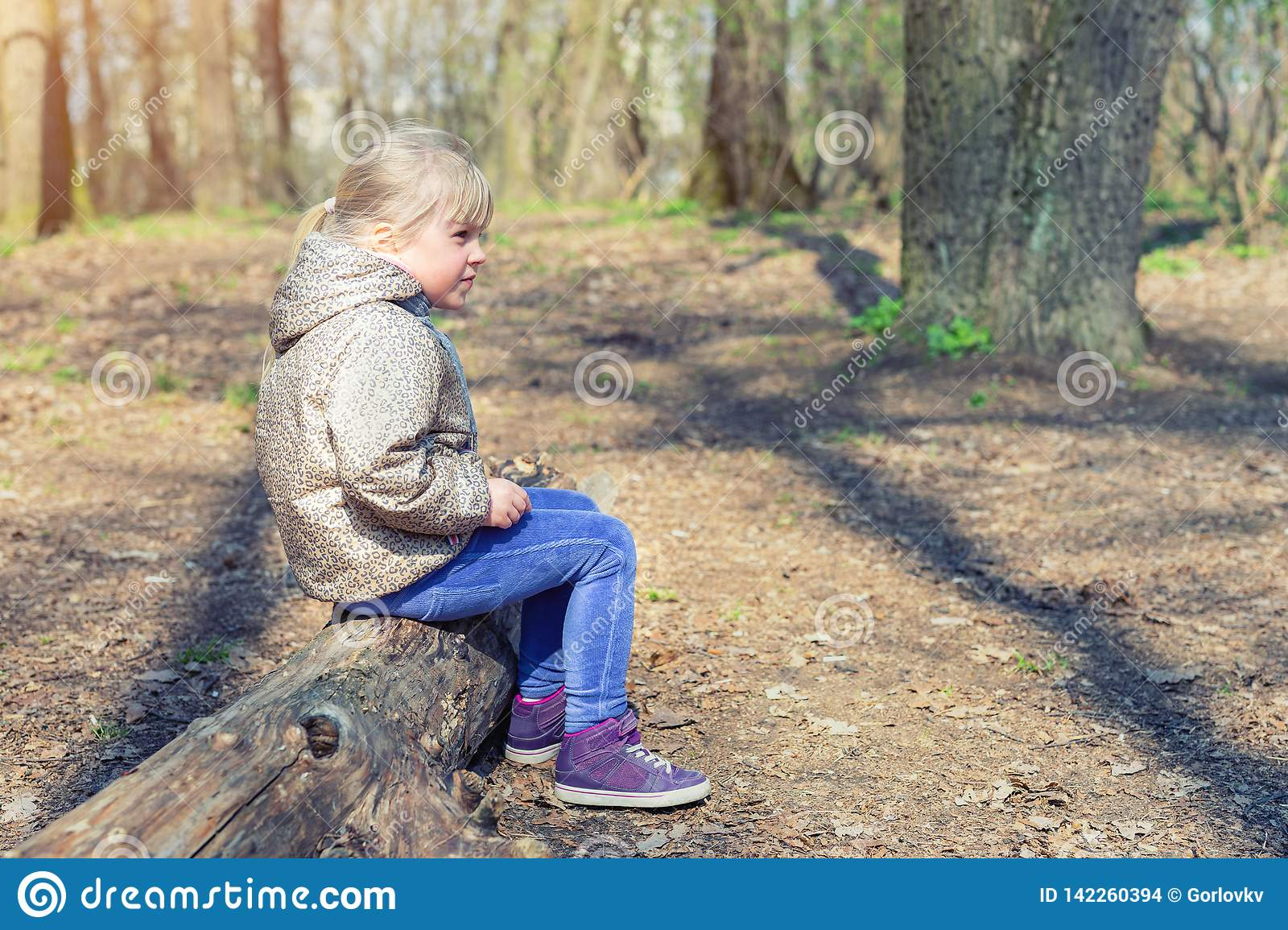 Cute little caucasian blond girl sittng on wooden log in forest and looking somewhere. Adorable pensive child dreaming about