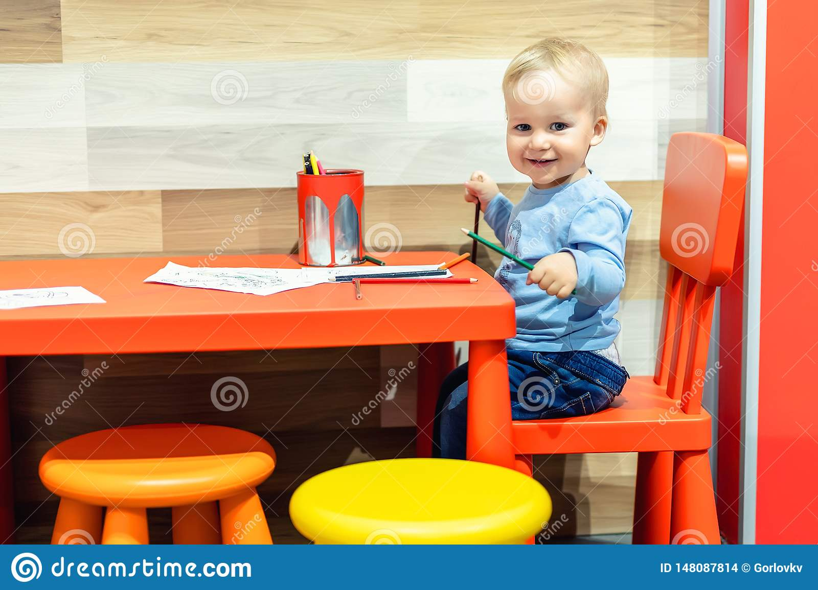 Cute little caucasian blond toddler boy sitting at table and drawing at children area at retail clothes store. Baby spending time
