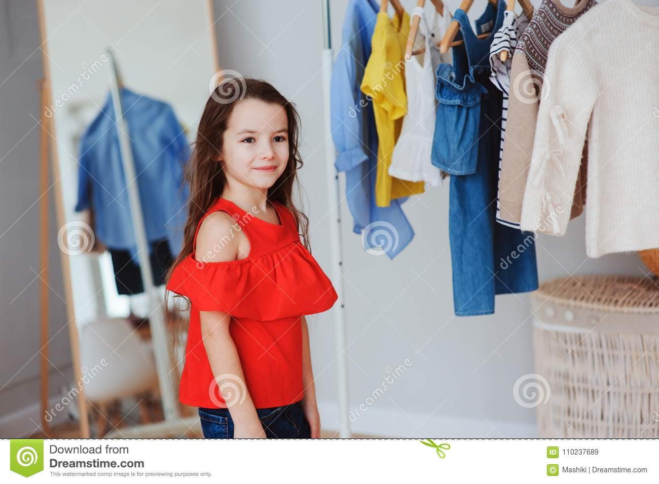dab84301e3ad Cute Little Child Girl Choosing New Modern Clothes In Her Wardrobe ...
