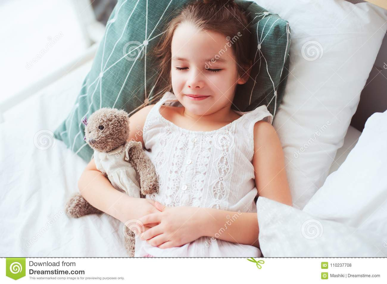 cute little child girl sleeping and watching sweet dreams with her teddy bear