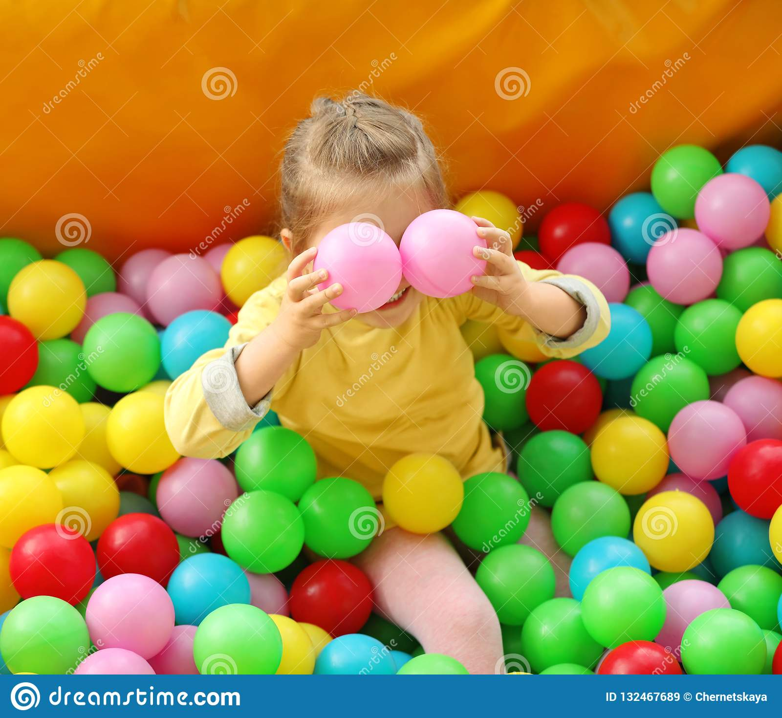 Cute little child playing in ball pit at amusement park