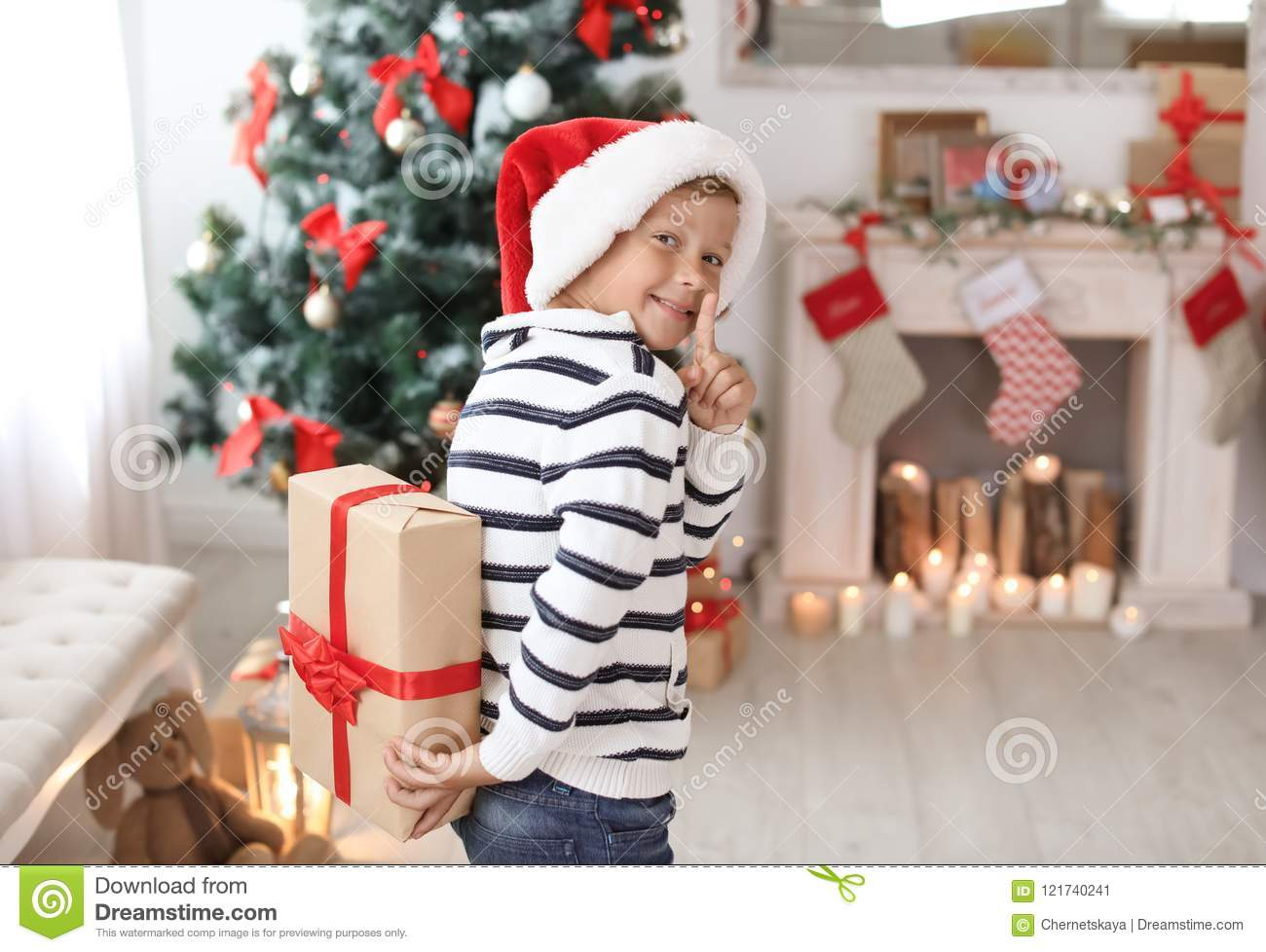 Cute Little Child In Santa Hat Hiding Christmas Gift Box Behind Back ...