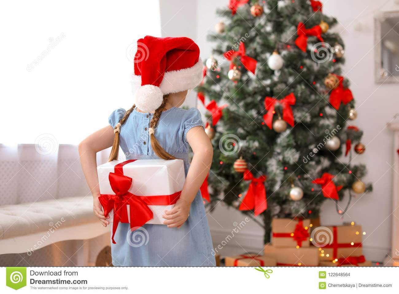 Cute Little Child In Santa Hat Hiding Christmas Gift Box Stock Photo ...