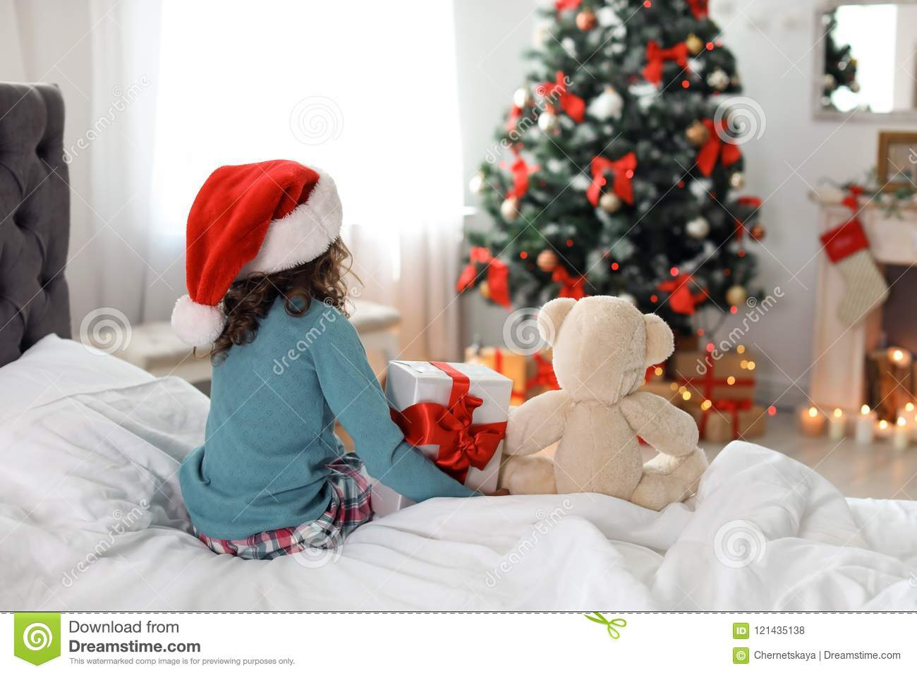 Cute Little Child In Santa Hat With Toy Bear And Christmas Gift Box ...