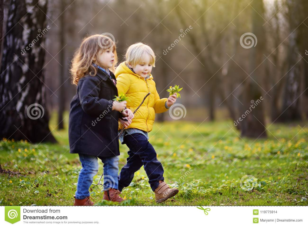 Cute little children playing together in sunny spring park