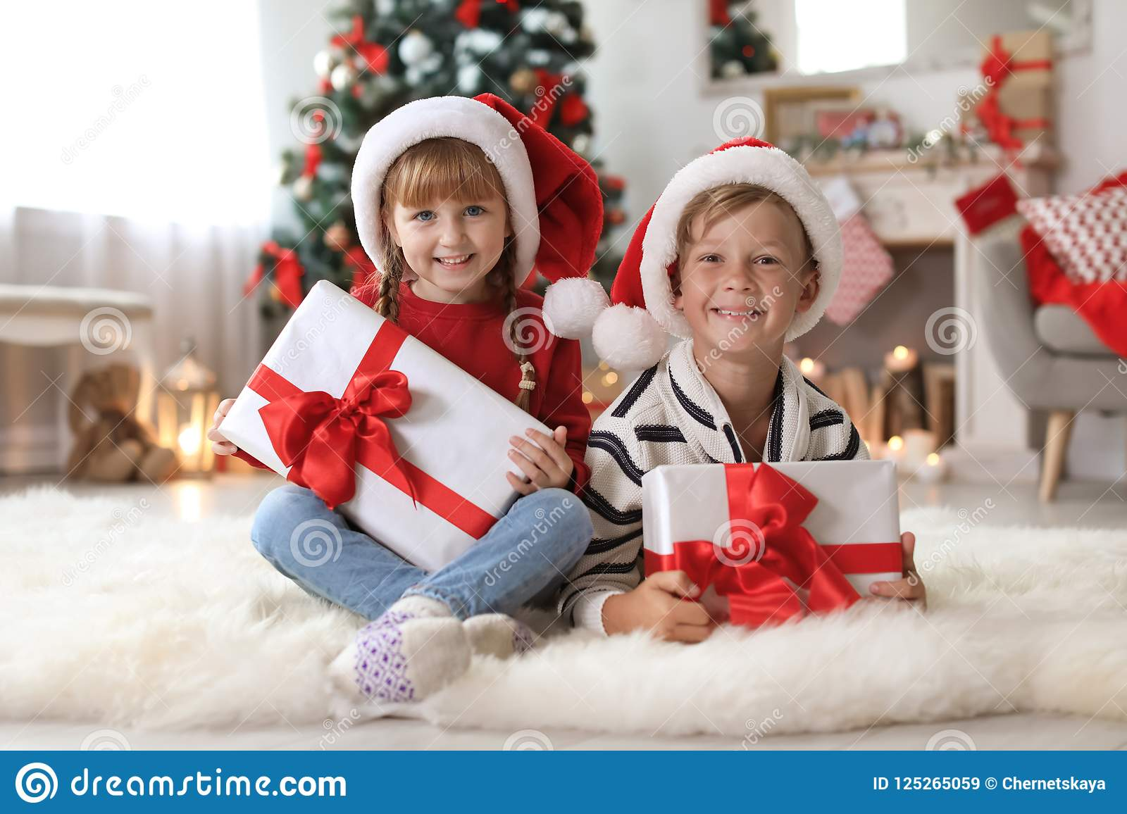 Cute Little Children In Santa Hats With Christmas Gift Stock Image ...