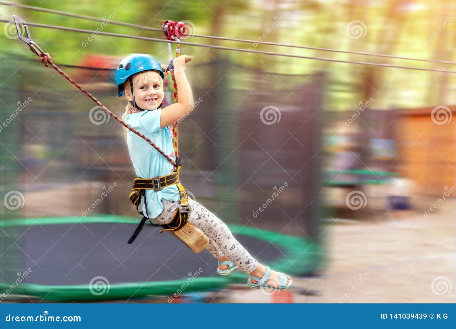 Cute little funny caucasion blond girl in helmet having fun riding rope zipline in adventure park. Children outdoor extreme sport