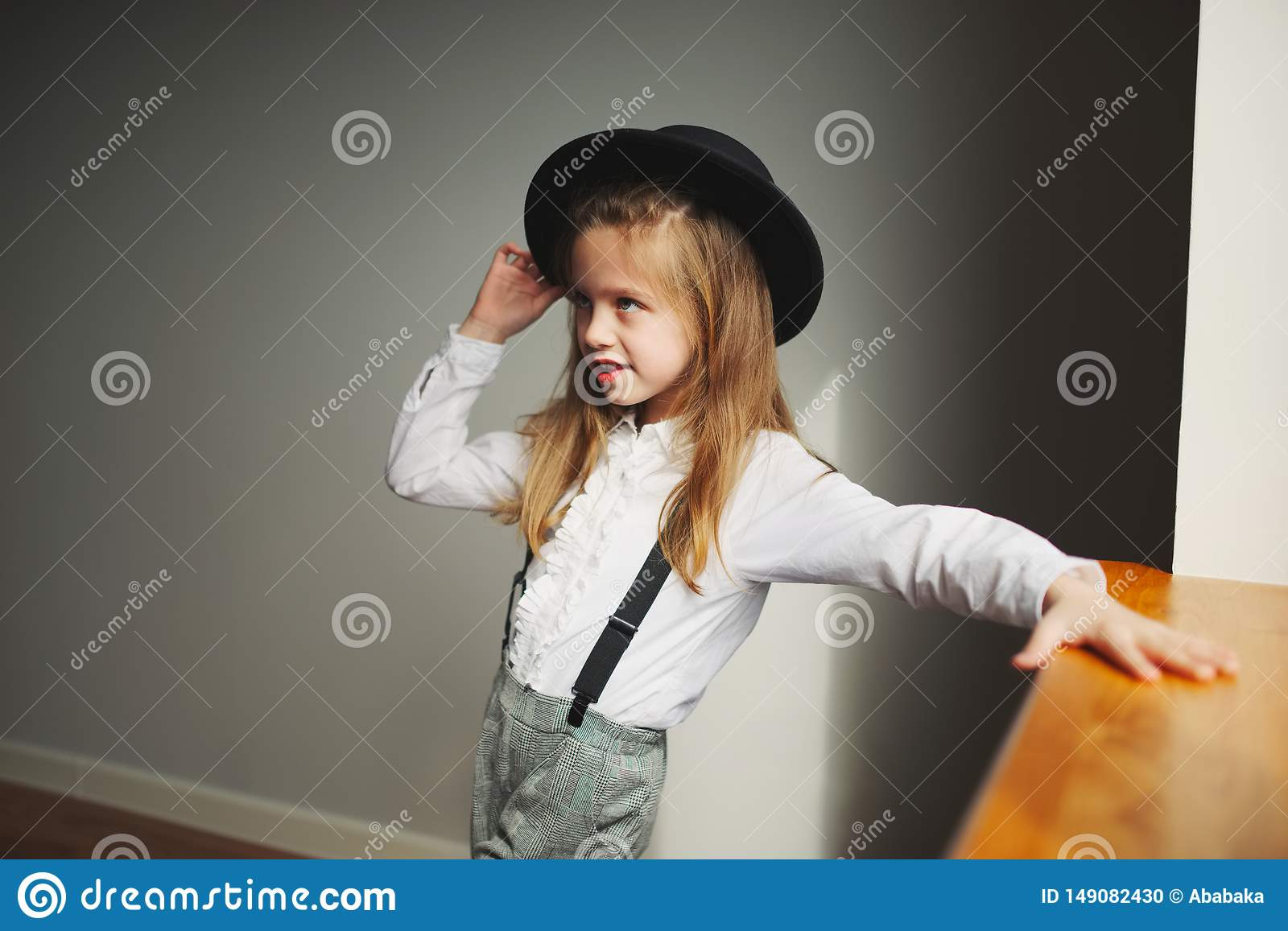 Cute little girl with black hat at home