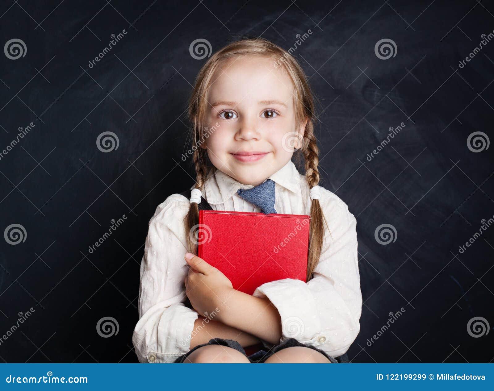 Cute little girl with book. Happy Child on empty blackboard