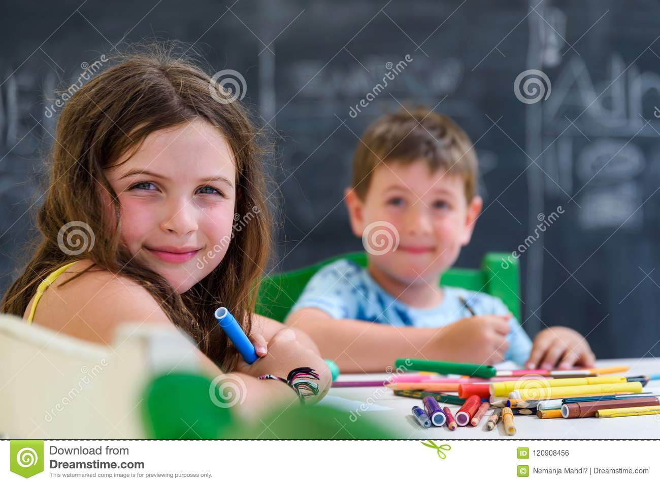 Cute little girl and boy drawing and painting with colorful markers pens at kindergarten. Creative activities kids club