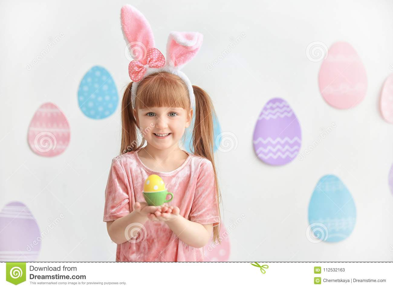 Cute little girl with bunny ears holding bright Easter egg