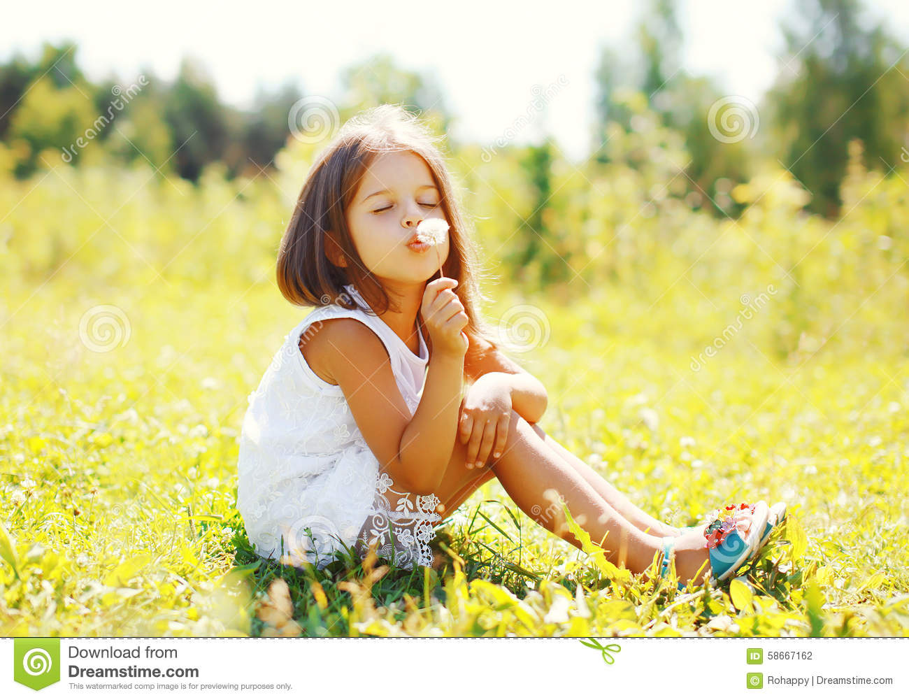 Cute Little Girl Child Blowing Dandelion Flower In Sunny