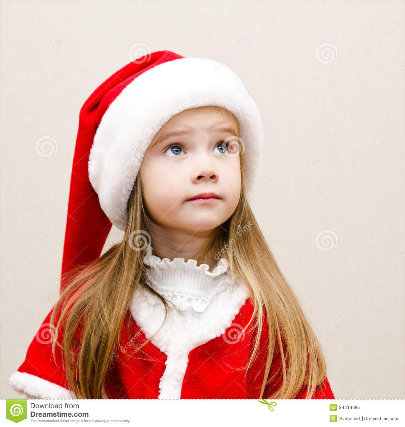 Cute Little Girl In Christmas Hat Dreaming And Looking Up