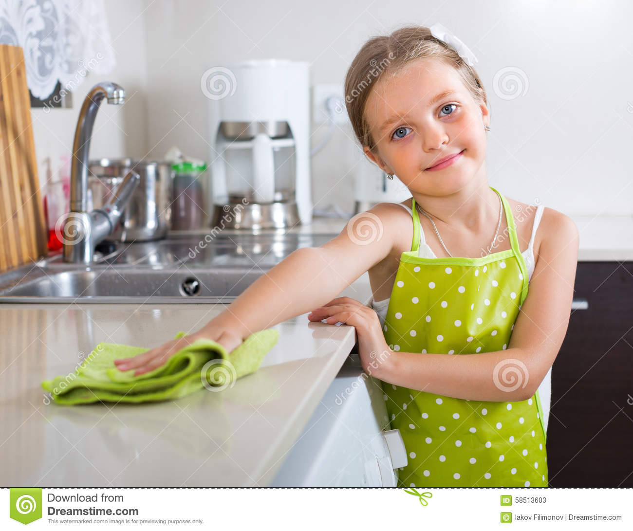Cute Little Girl Cleaning At Kitchen Stock Image