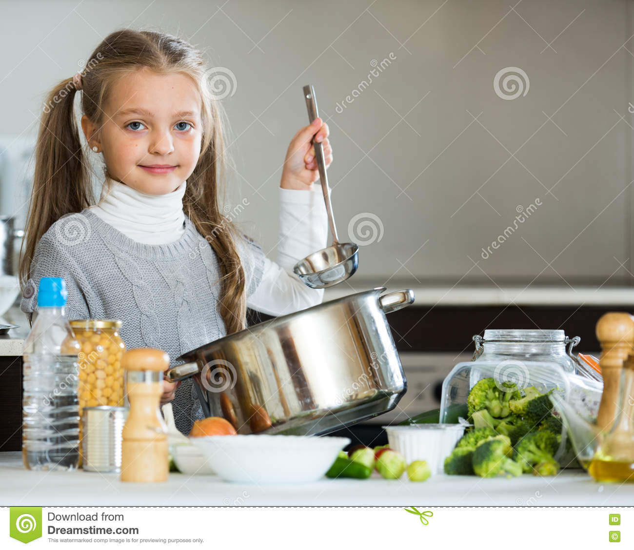 Cute Little Girl Cooking Veggies In Kitchen Royalty-Free