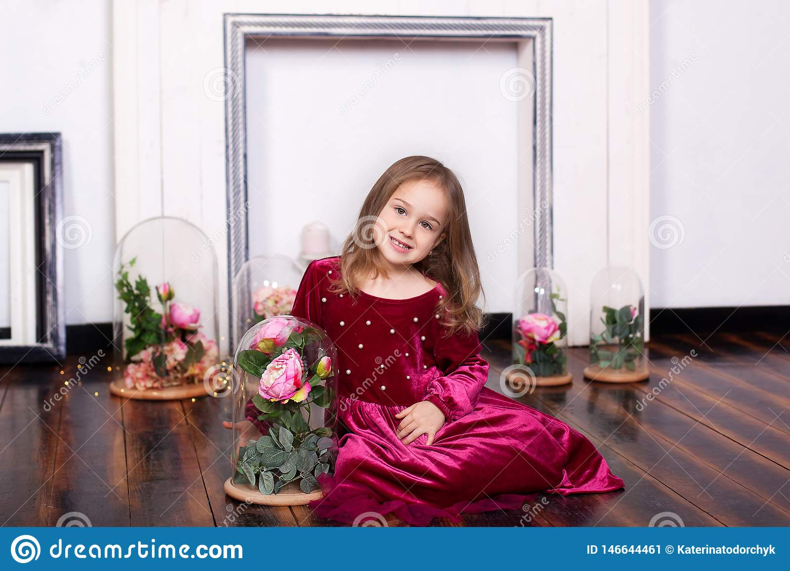 A cute little girl in a dress is sitting on the floor with a rose in a flask. Looking at the camera. Childhood. Sweet princess. Th