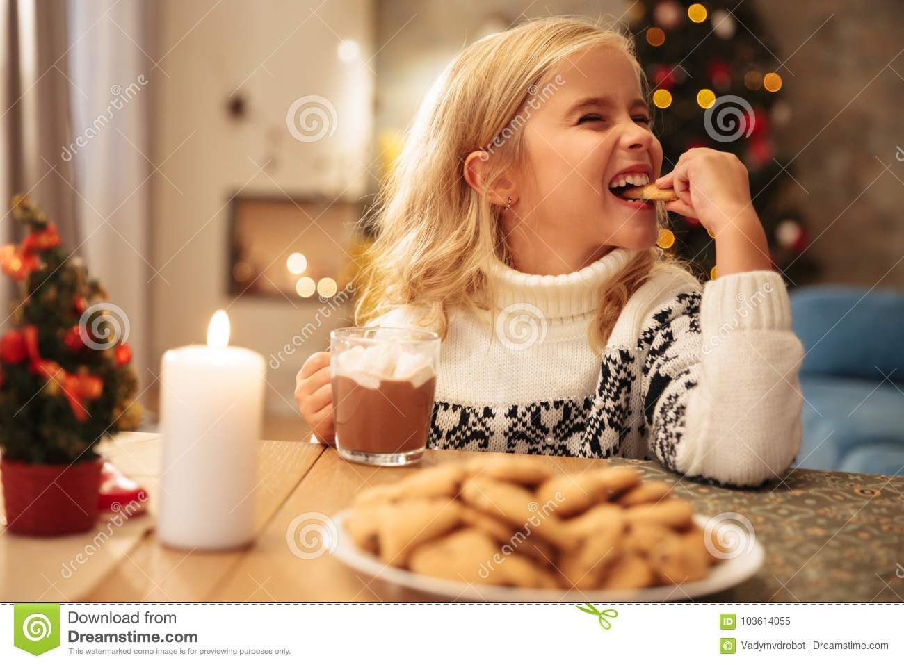 Cute little girl drinking cacao and eating cookie at home