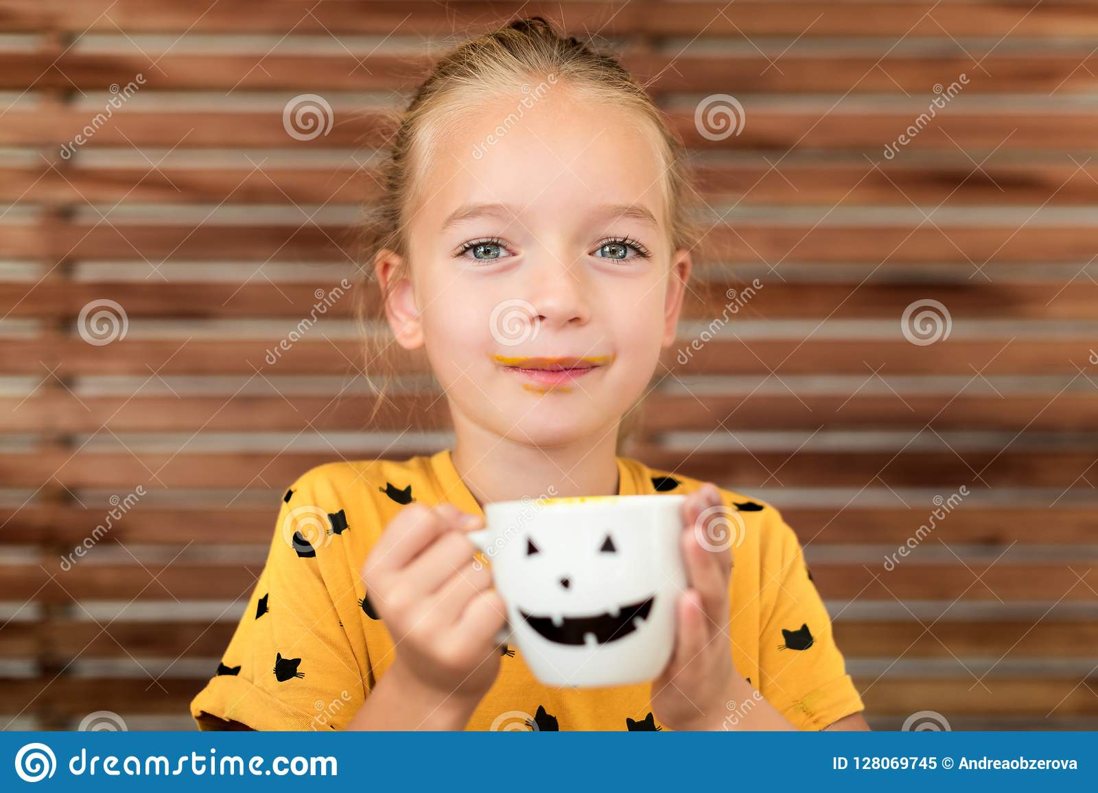 Cute little girl drinking pumpkin soup out of a cup with Halloween anthropomorphic smiley face. Halloween conceptual background.
