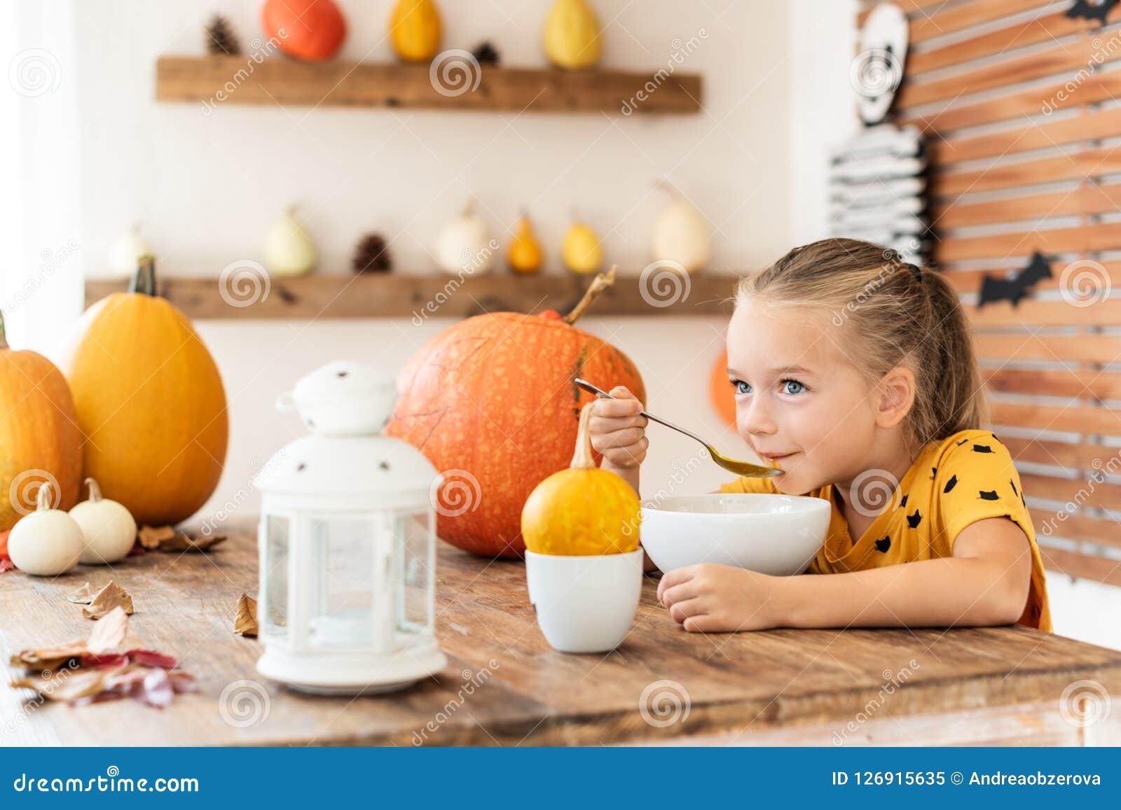 Cute little girl eating pumpkin soup in Halloween decorated dinning room. Autumn season comfort food.