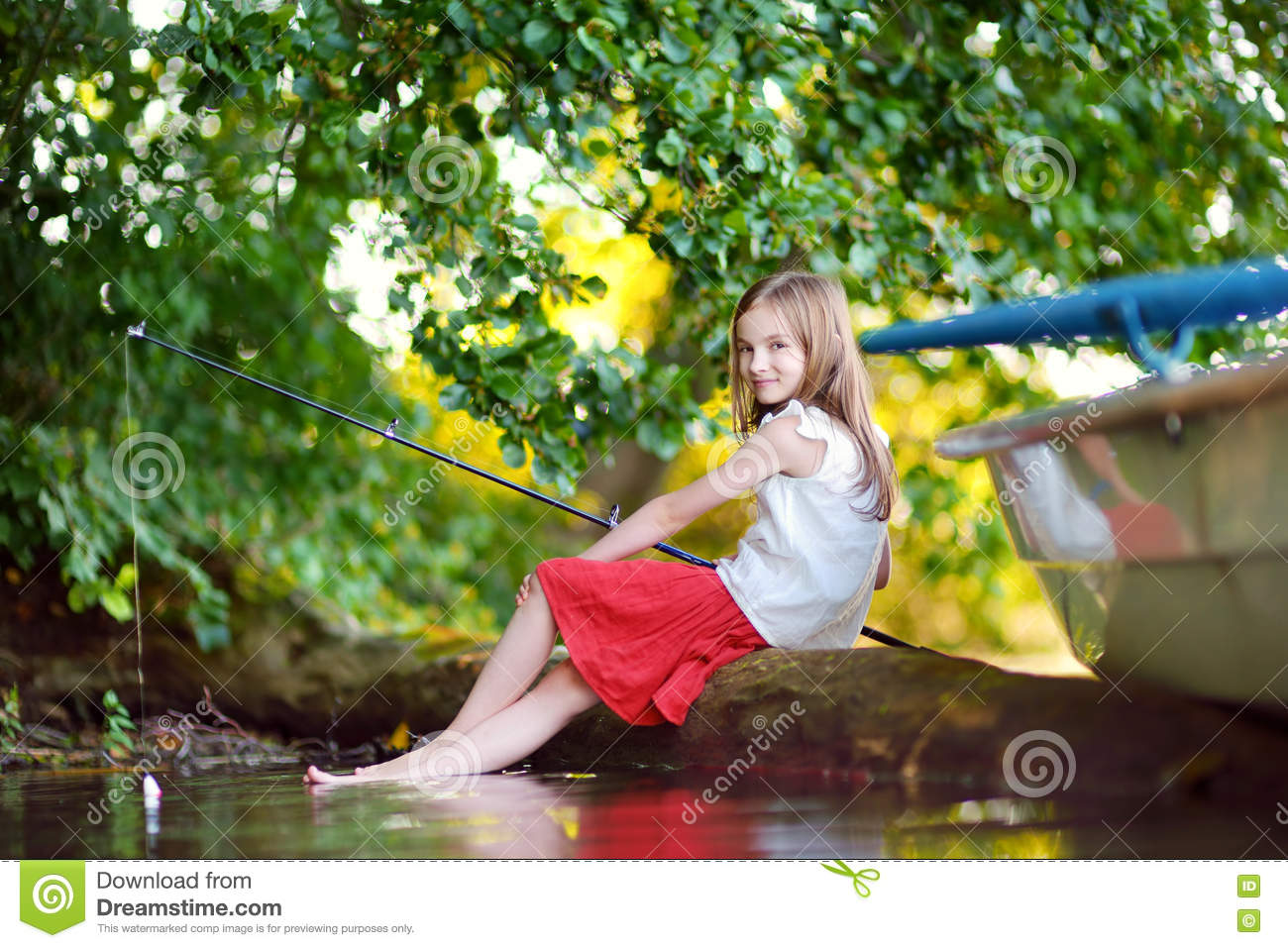 Cute little girl fishing with a fishing rod by a river for Little girl fishing pole