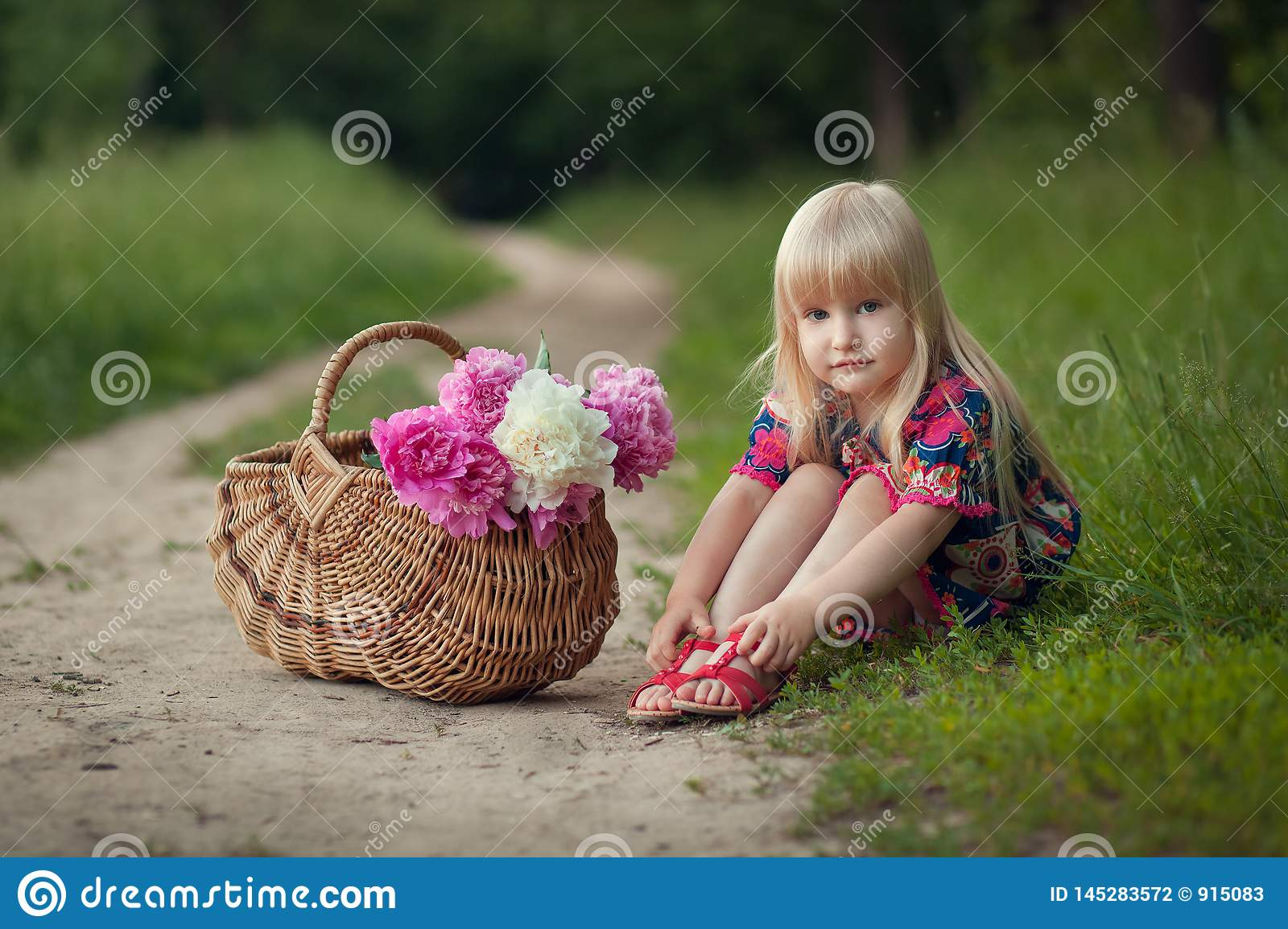 Cute little girl on a forest road with a basket of flowers. The concept of carefree childhood