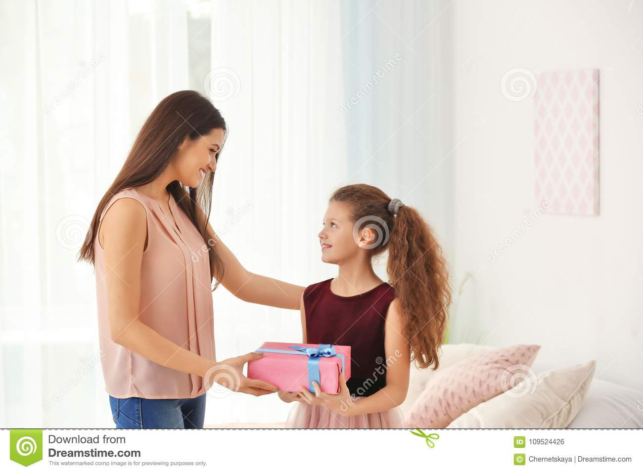 Cute little girl giving gift box to her mom indoors.
