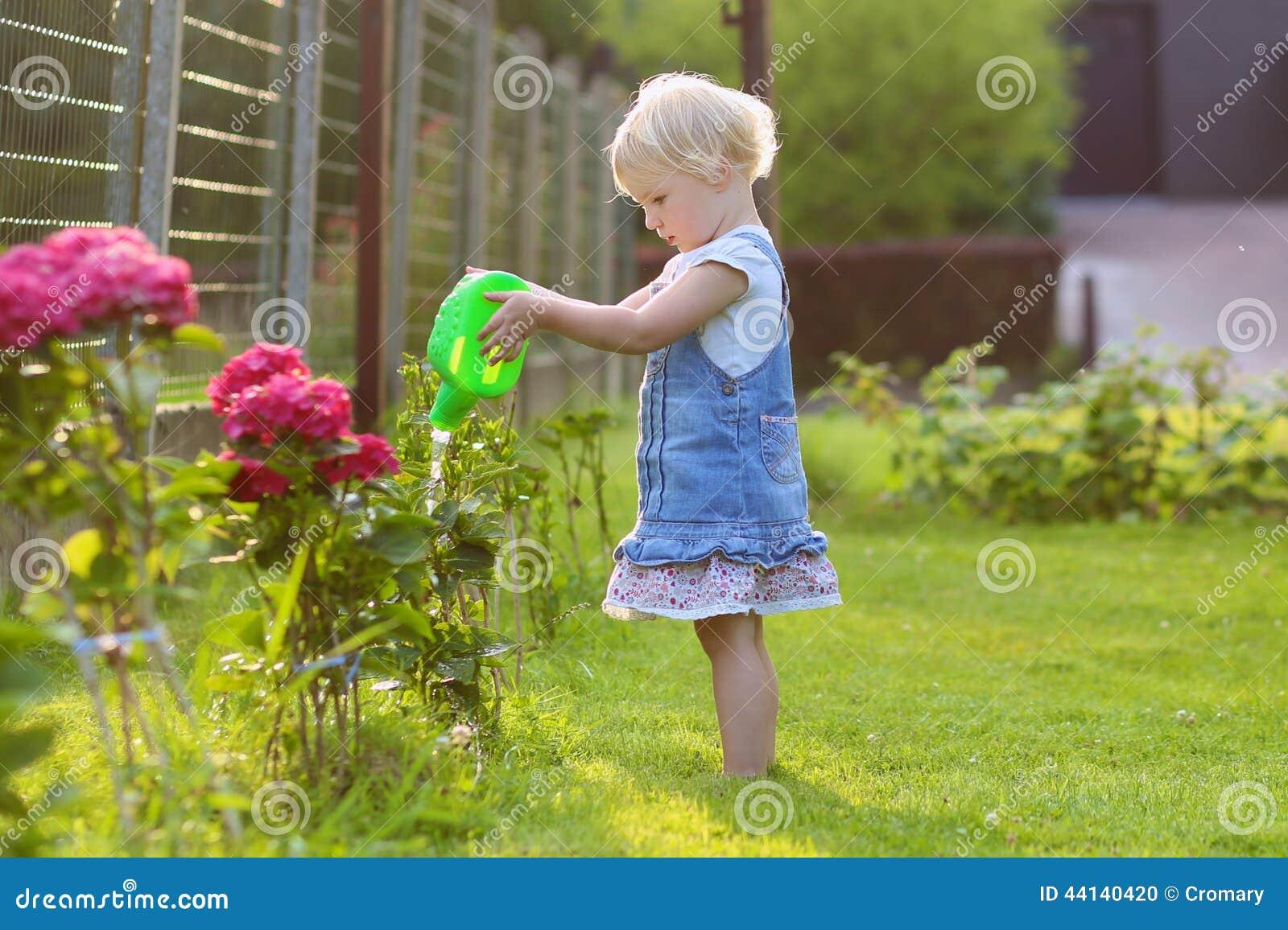 Cute little girl giving water garden flowers