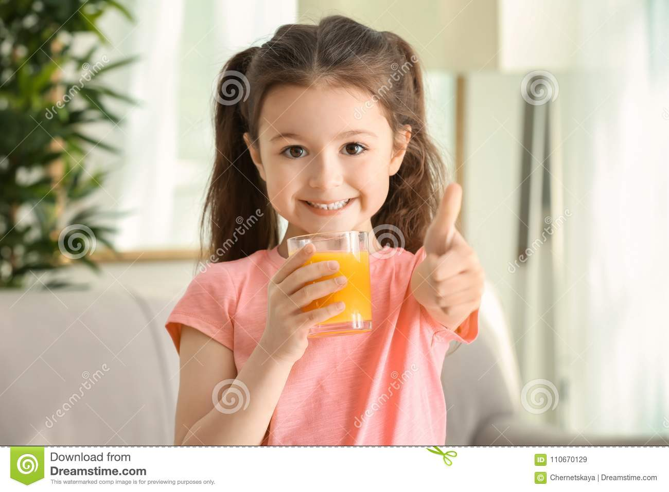 Cute little girl with glass of juice