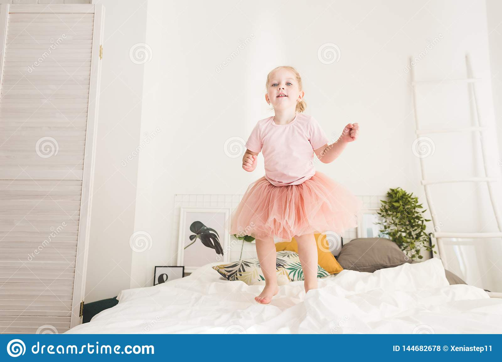 Cute little girl have fun on the bed at home.