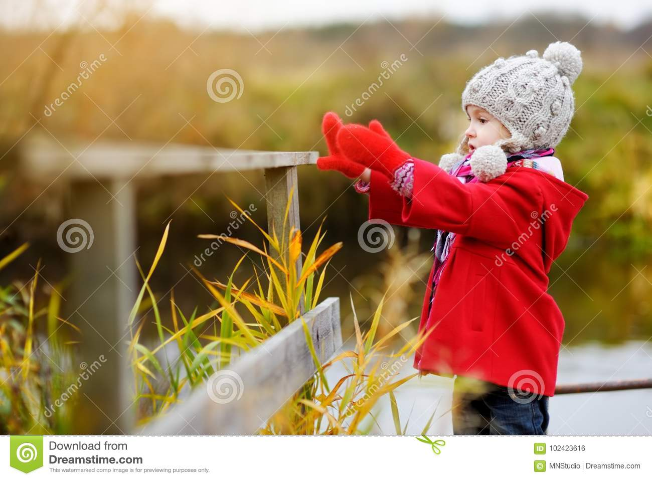 Cute little girl having fun on beautiful autumn day. Happy child playing in autumn park. Kid gathering yellow fall foliage.