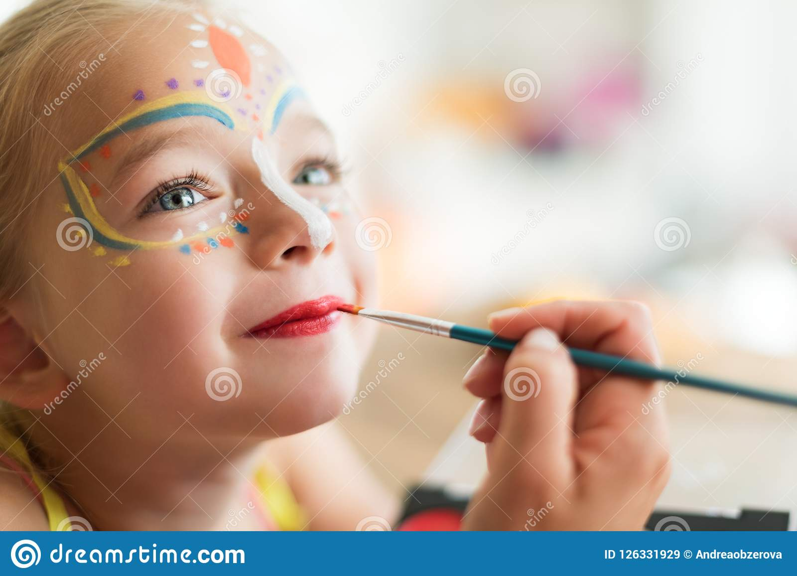 Cute little girl having her face painted for Halloween party. Halloween or carnival family lifestyle background. Face painting.