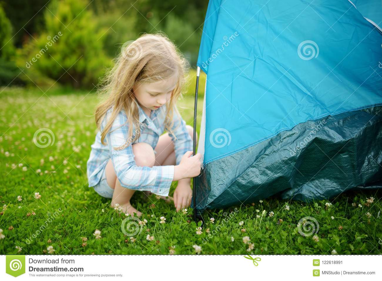 Cute little girl helping her parents to set up a tent on a campsite.