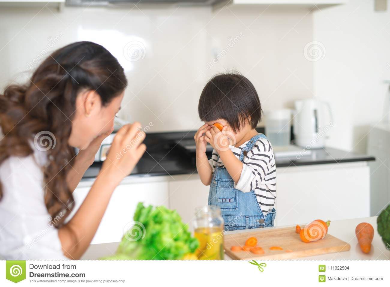 Cute little girl and her beautiful mother drinking milk and eating cookies