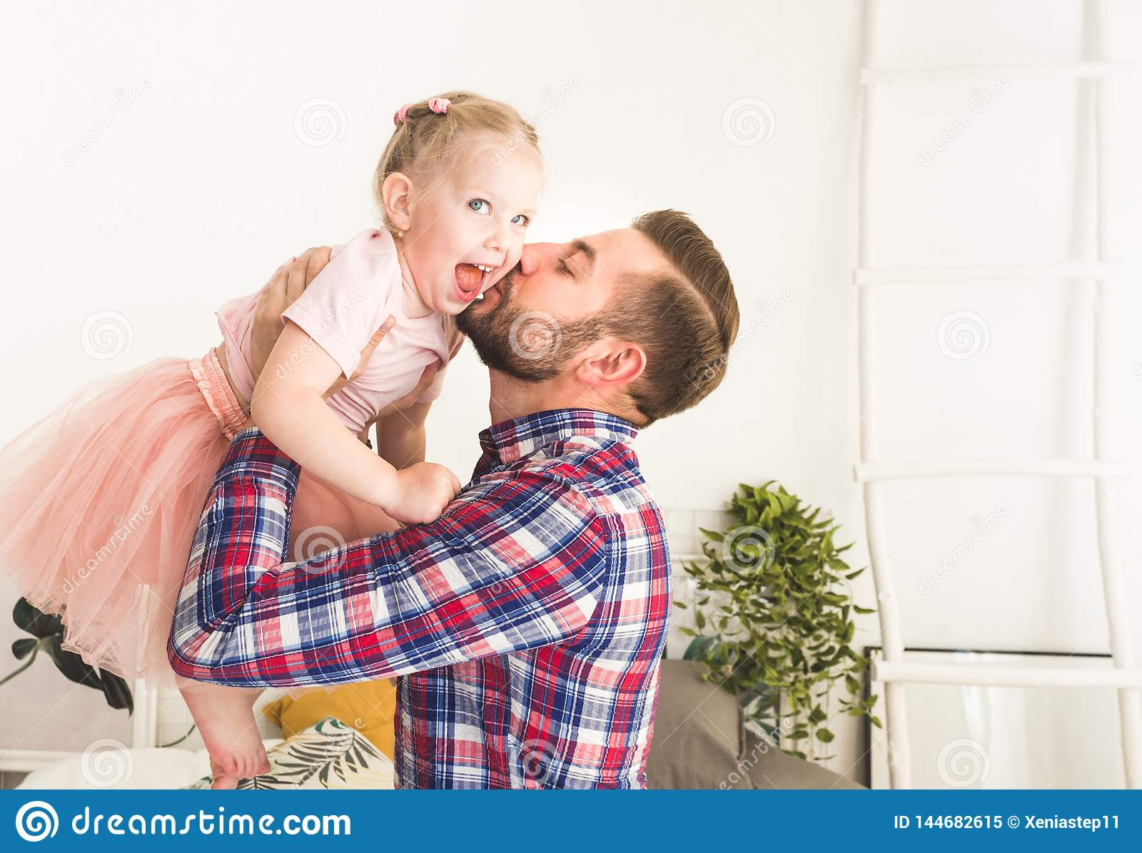 Cute little girl and her dad are having fun at home.